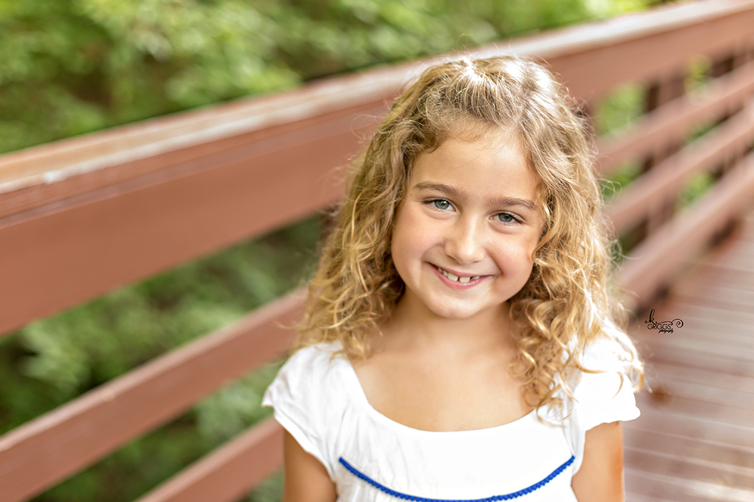 Young girl in white dress on bridge smiling. | St. Louis Family Photographer