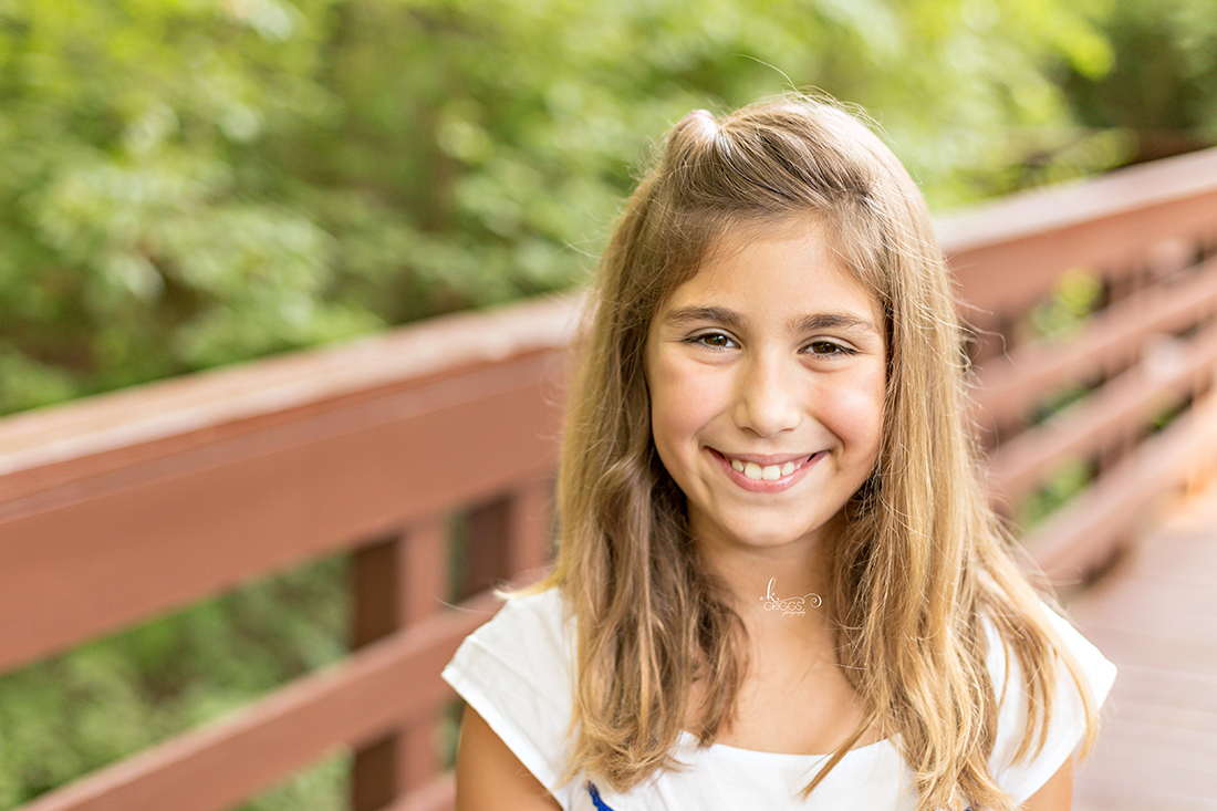 Pre teen girl in white dress smiling at camera | St. Louis Children's Photographer