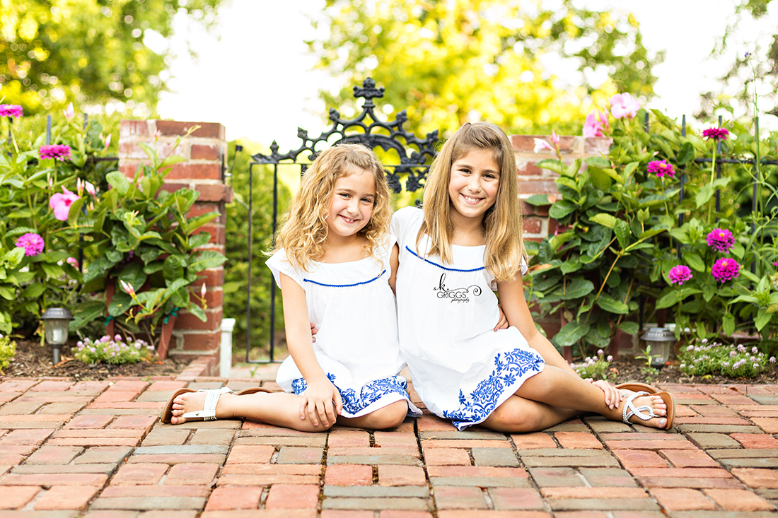 Two girls sitting on the ground smiling at camera. | St. Louis Family Photography