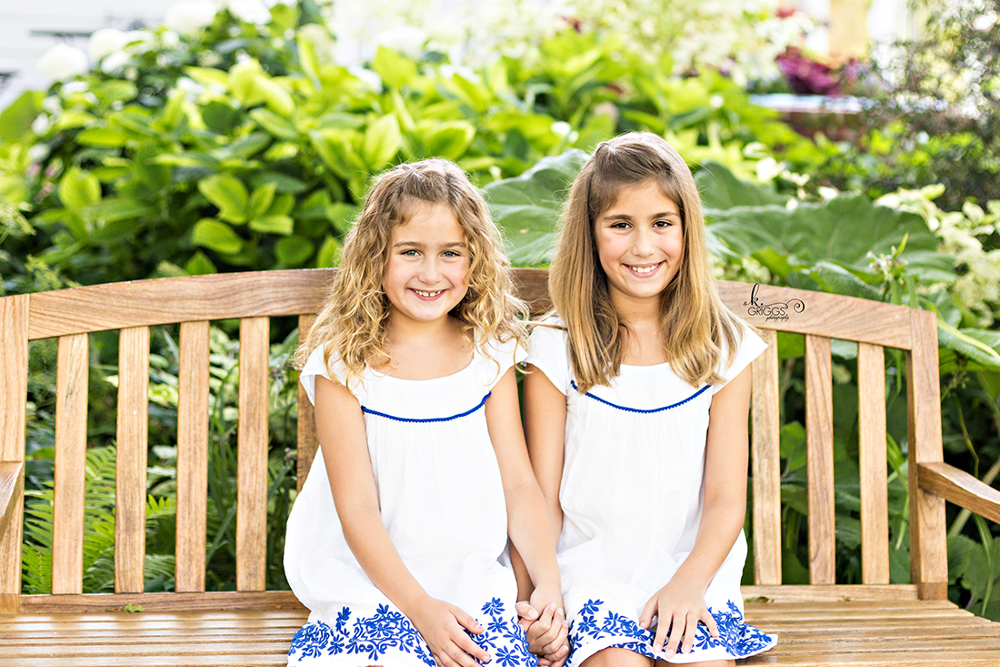 Sisters sitting on a bench in a garden. | St. Louis Family Portraits