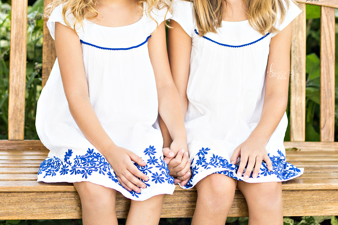 Sisters holding hands sitting on bench | St. Louis Family Photos