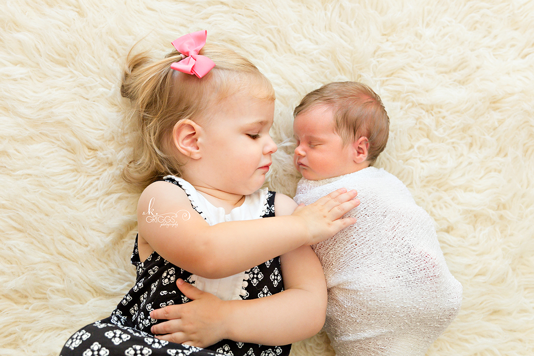 Big sister touching brand new baby sister | St Louis Newborn Photographer