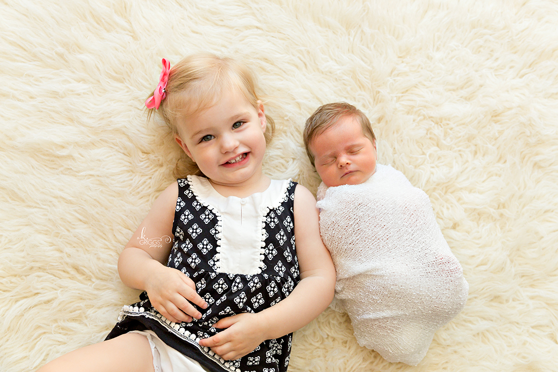 Big sister with baby sister on rug | St. Louis Newborn Photography
