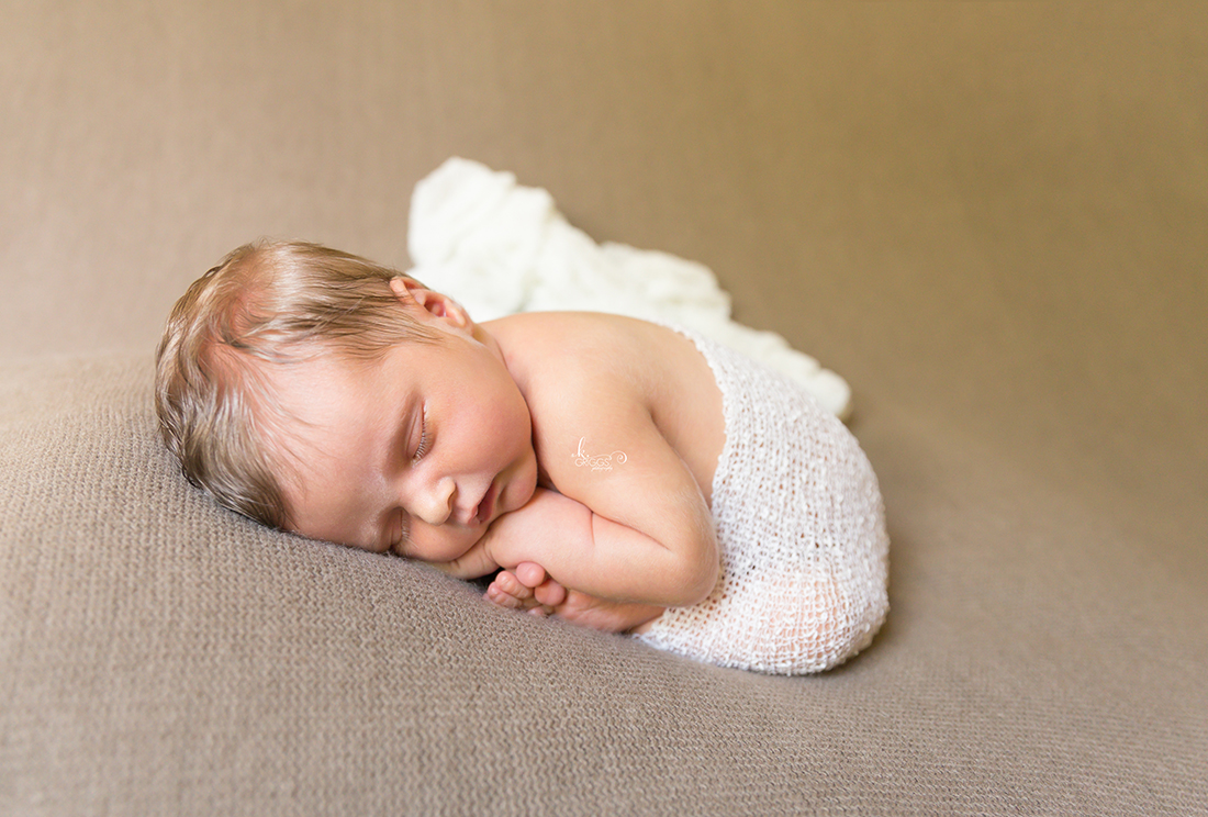Newborn baby with white wrap on a brown blanket | St. Louis Photography