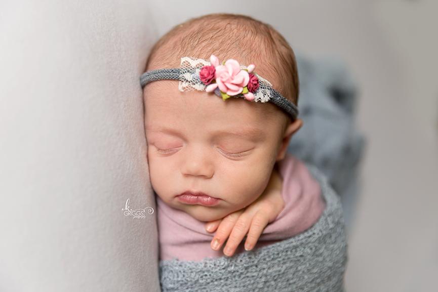 Newborn girl sleeping wearing headband. | St. Louis Newborn Photography