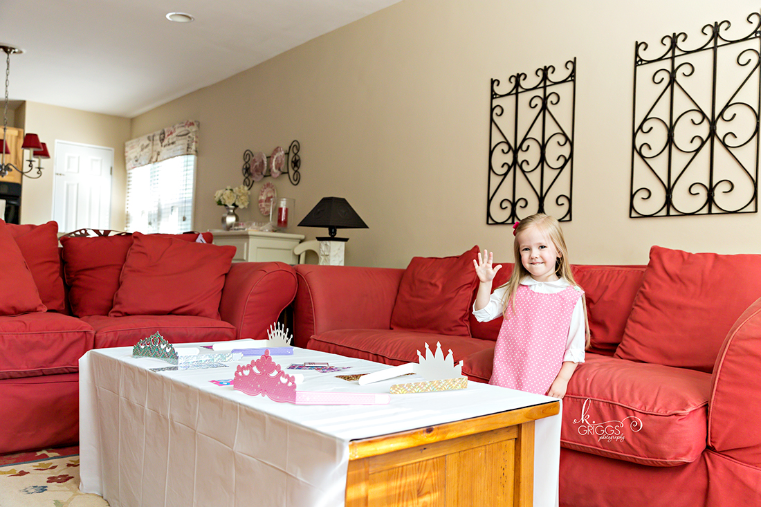 Little girl standing in living room holding up her hand | Family Photographer St. Louis