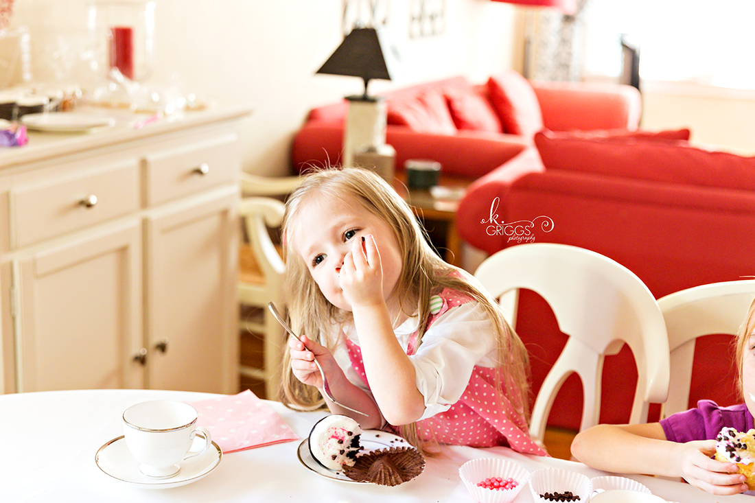 Little girl sitting at table eating cupcake | St. Louis Photography