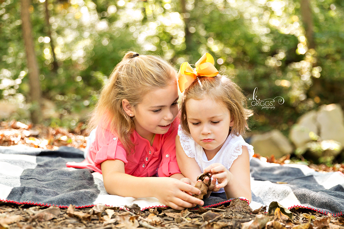 Sweet sisters laying on a blanket Longview Farm Park | St. Louis Family Photographer