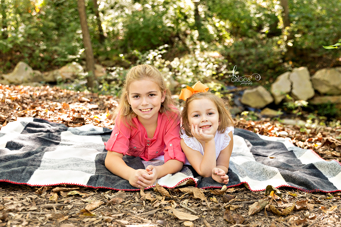 Sisters laying on blanket smiling at camera | St. Louis Family Photographer