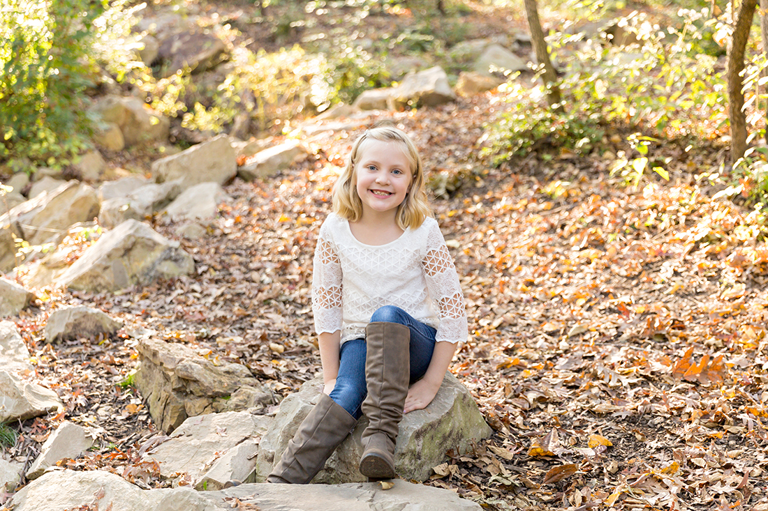Girl sitting on rock smiling at camera - Longview Farm Park | St. Louis Family Photographer