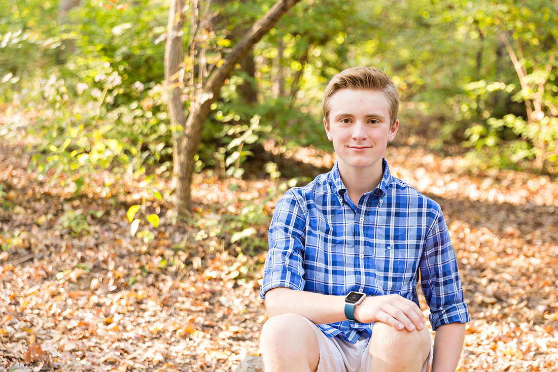 Teenage boy sitting on ground smiling - Longview Farm Park | St. Louis Family Photos