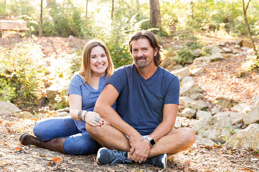 Husband and wife sitting on ground in park - Longview Farm Park | St. Louis Family Photographer