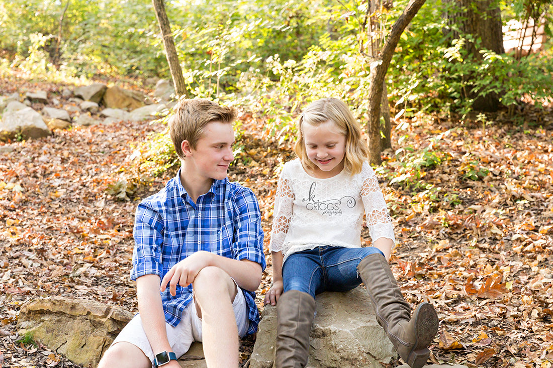 brother and sister sitting on rocks in Longview Farm Park | St. Louis Family Photographer