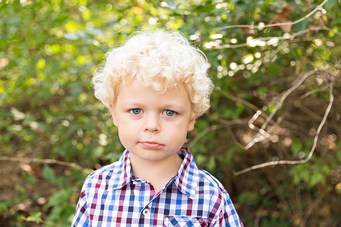 Young boy looking at camera with smirk on face - Longview Farm Park | St. Louis Photographer