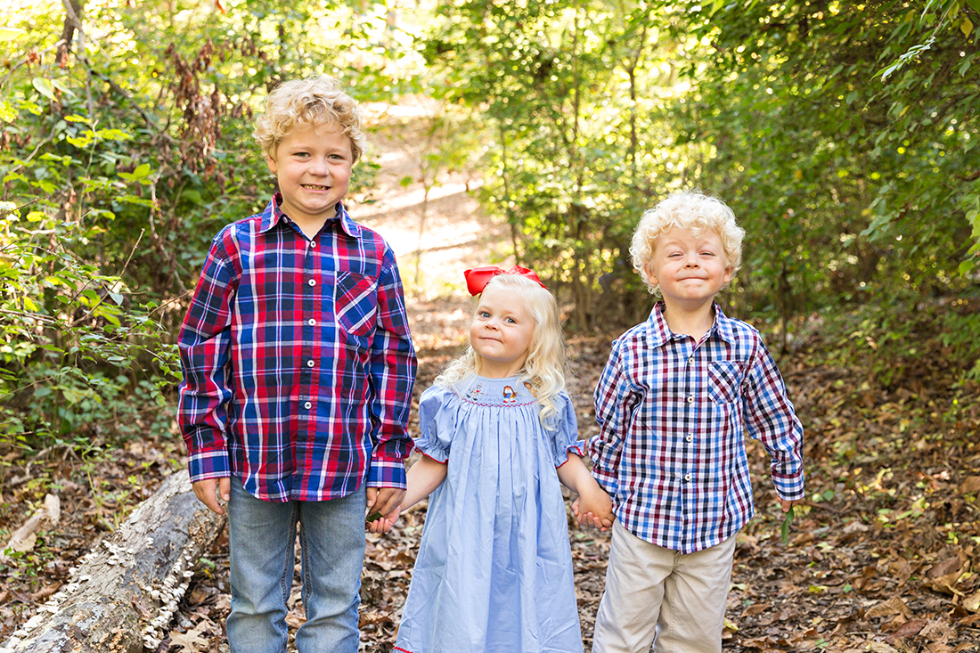 Three children holding hands in wooded area - Longview Farm Park | St. Louis Family Photographer