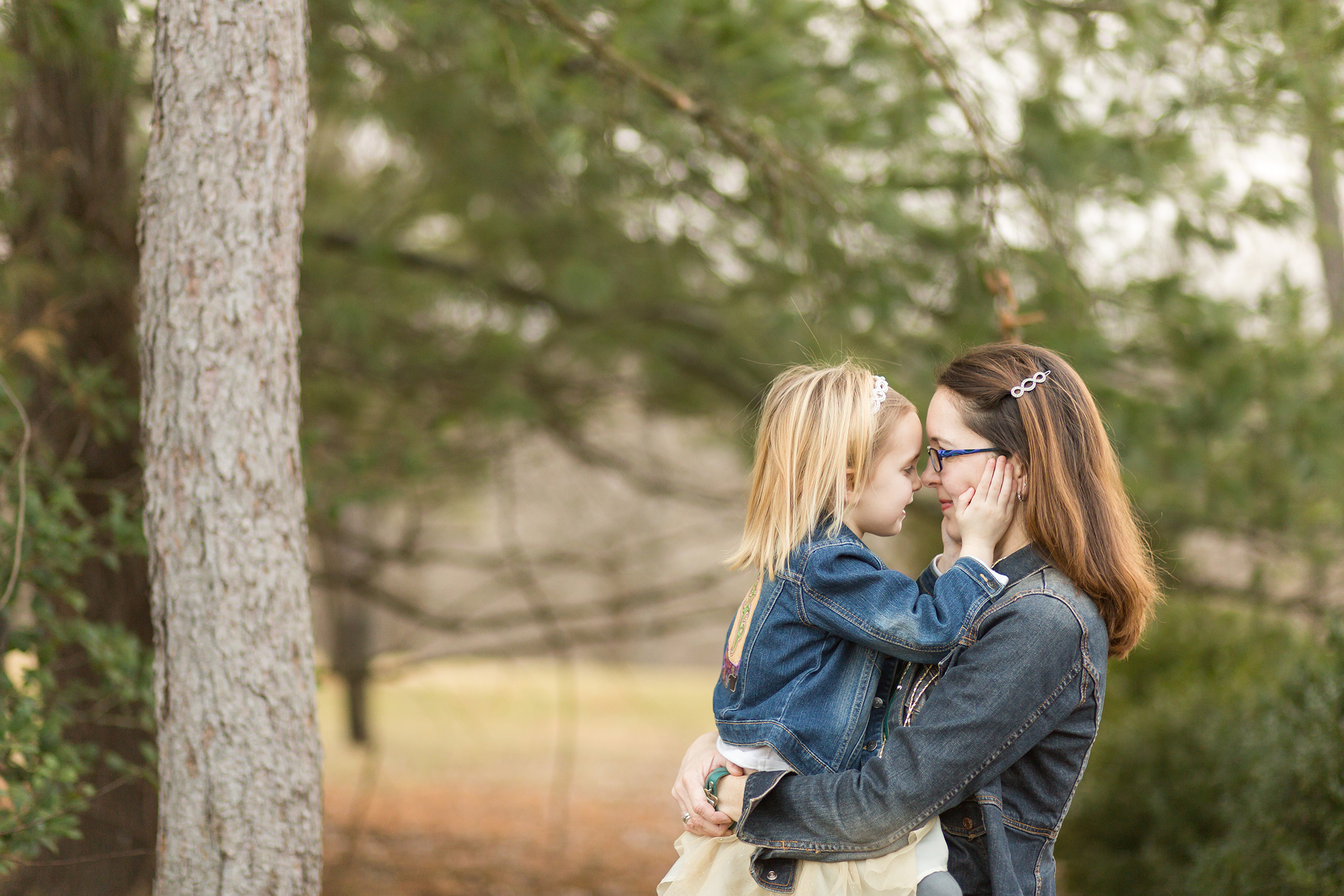 Mom holding daughter while they are looking at each other | St. Louis Family Photographer