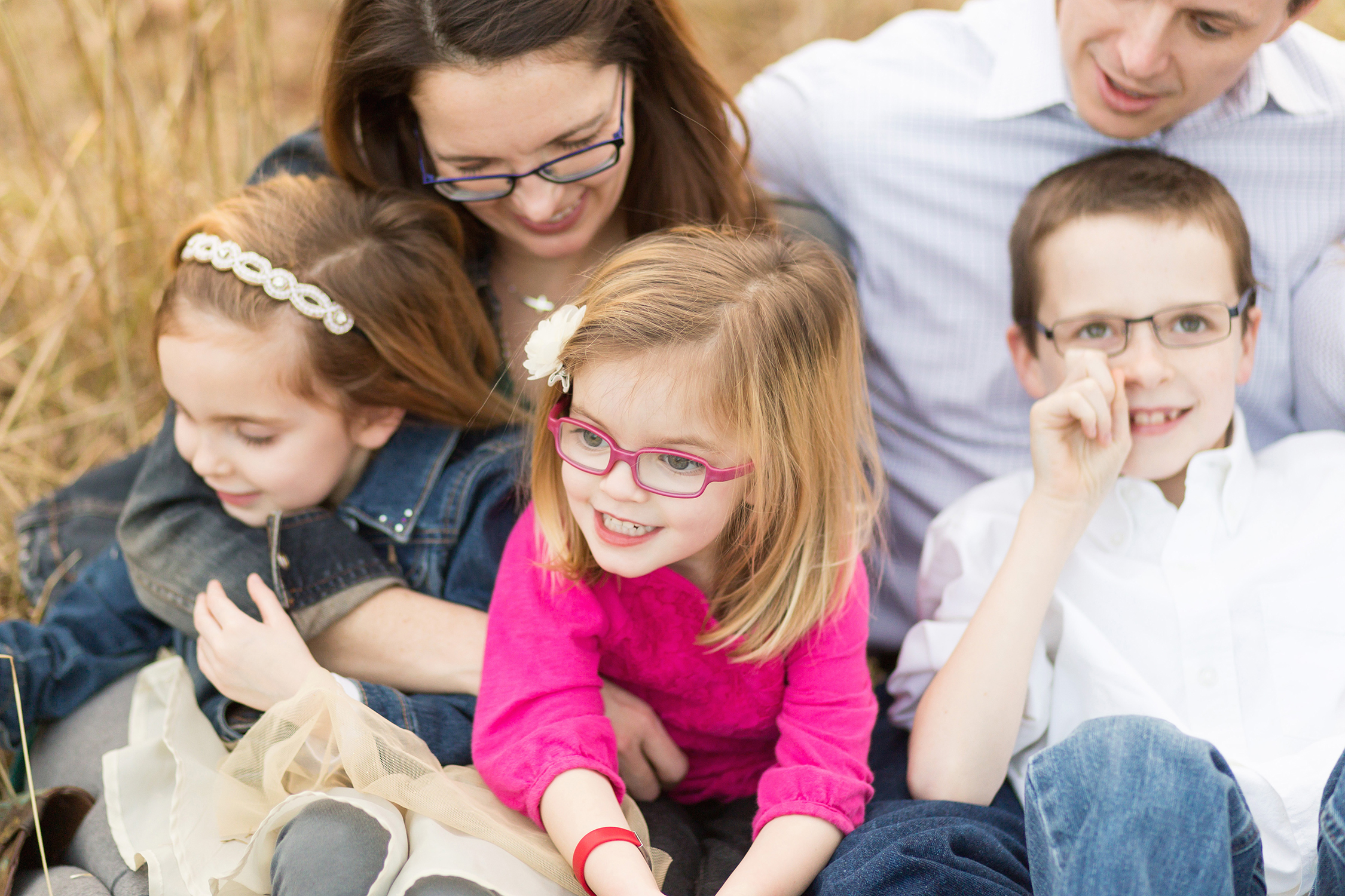 Young girl wearing pink glasses sitting with her family. | Kirkwood Photographer