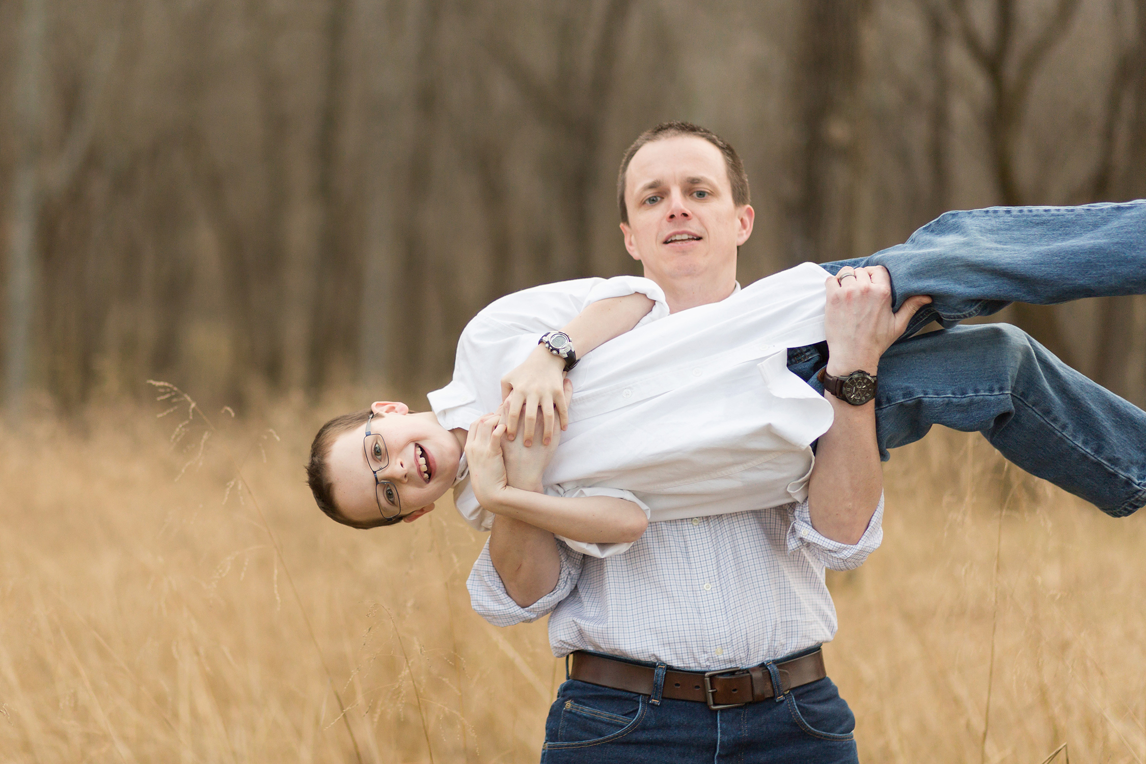 Father picking up young son in playful way | St. Louis Family Photography