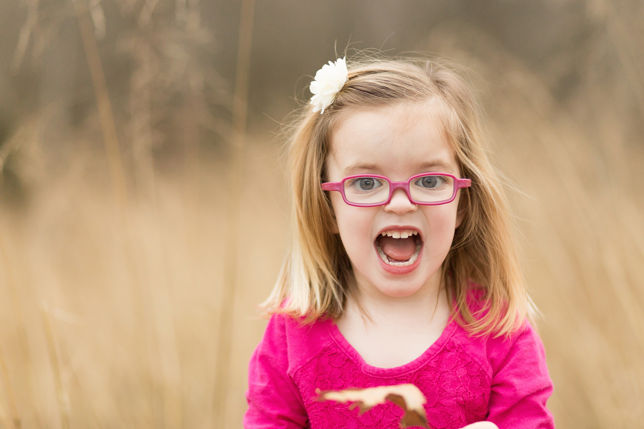 Young girl wearing pink glasses with her mouth open | St. Louis Children's Photography