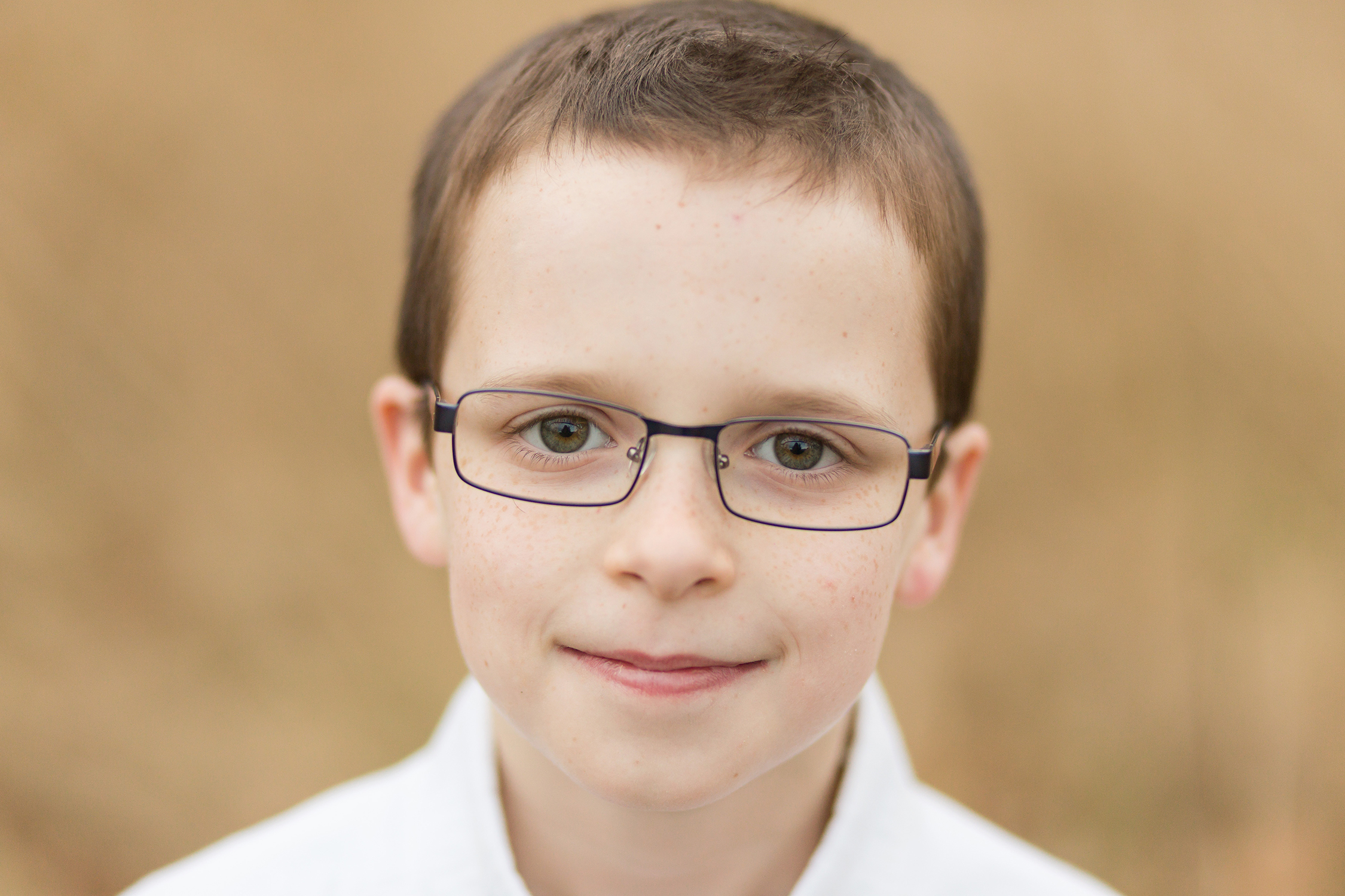 Young boy wearing glasses looking at camera | Kirkwood Family Photographer