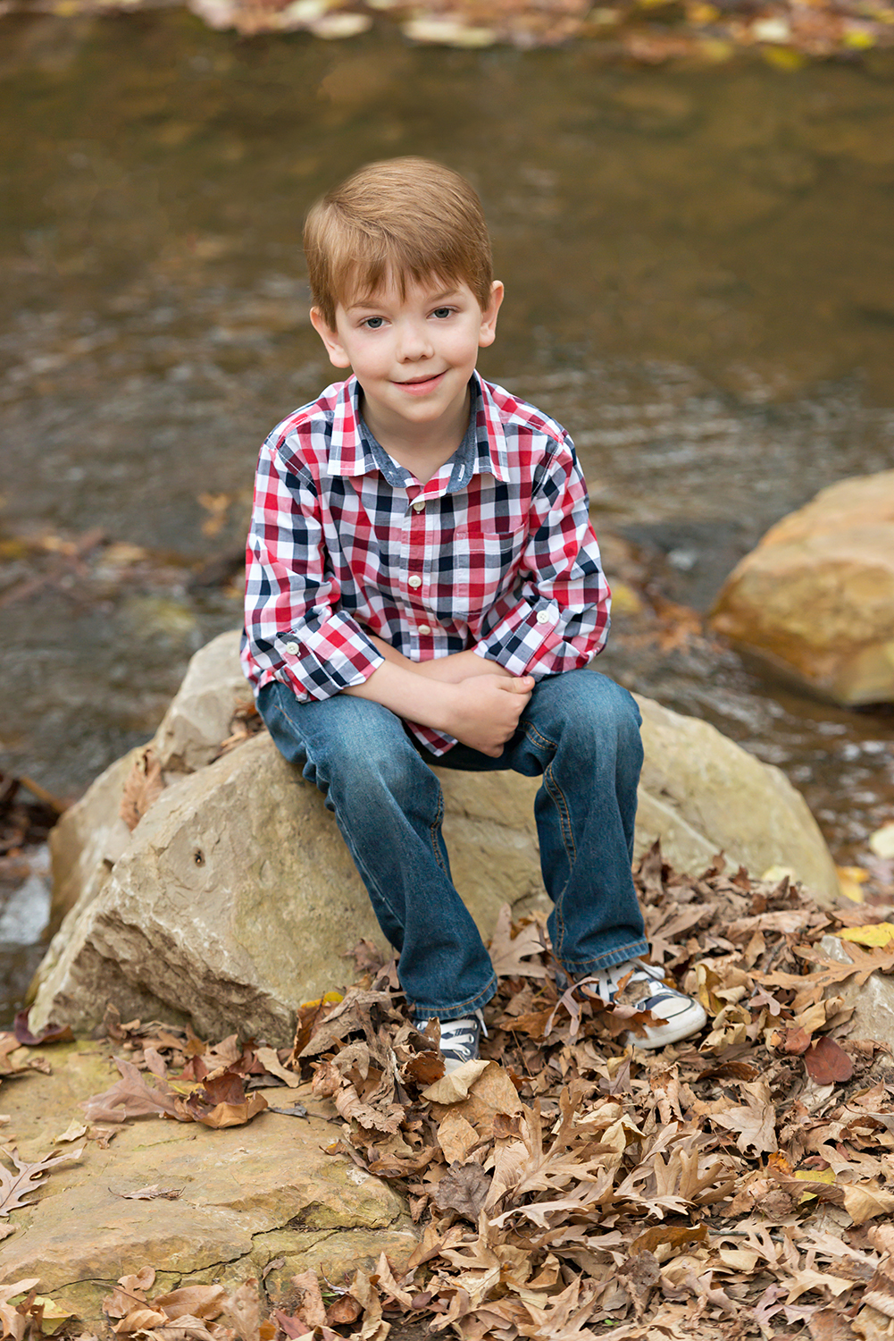 Young boy sitting by a stream | St. Louis Photography