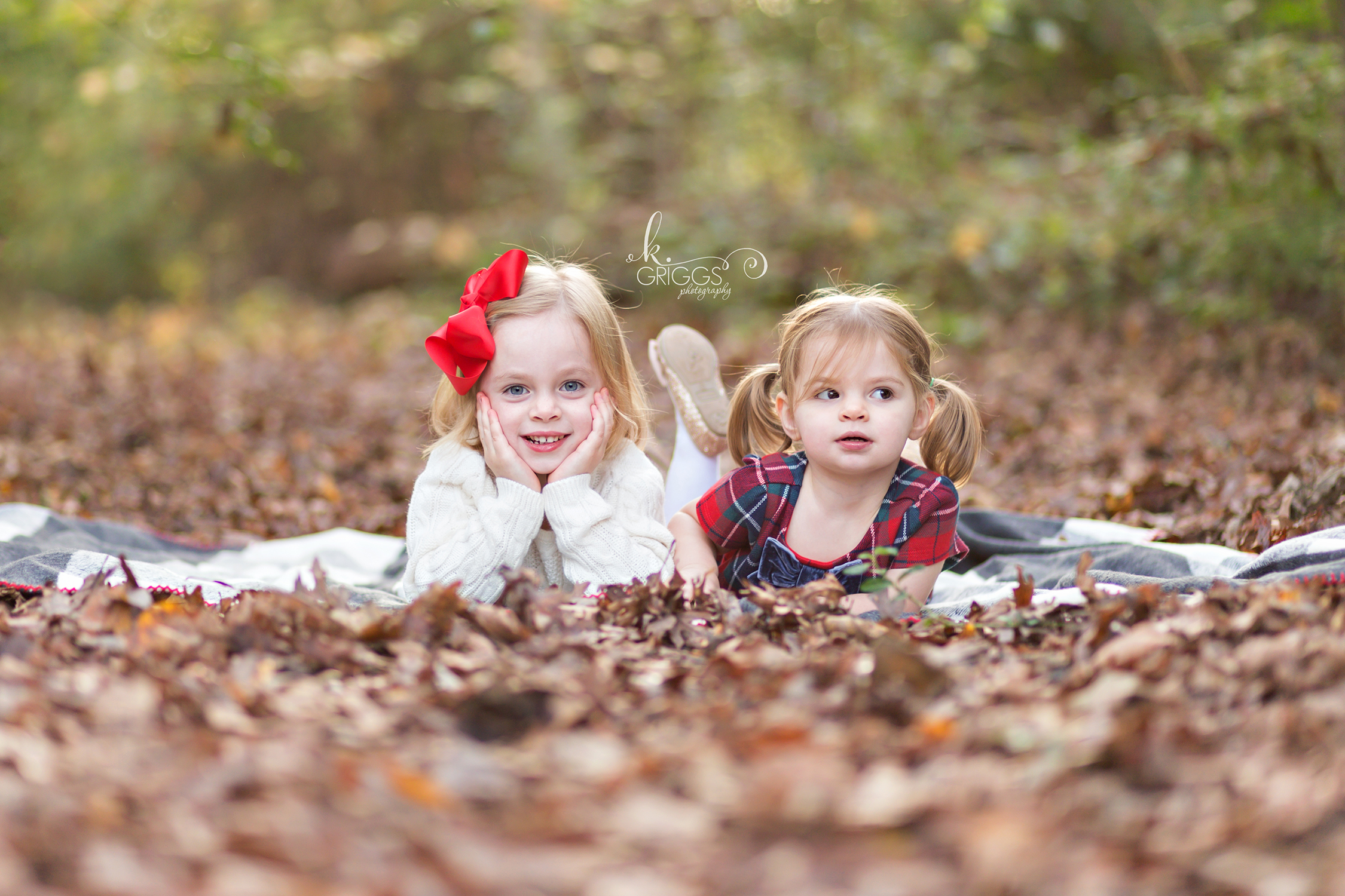 Sisters laying on a blanket on a bed of leaves | St. Louis Children's Photographer