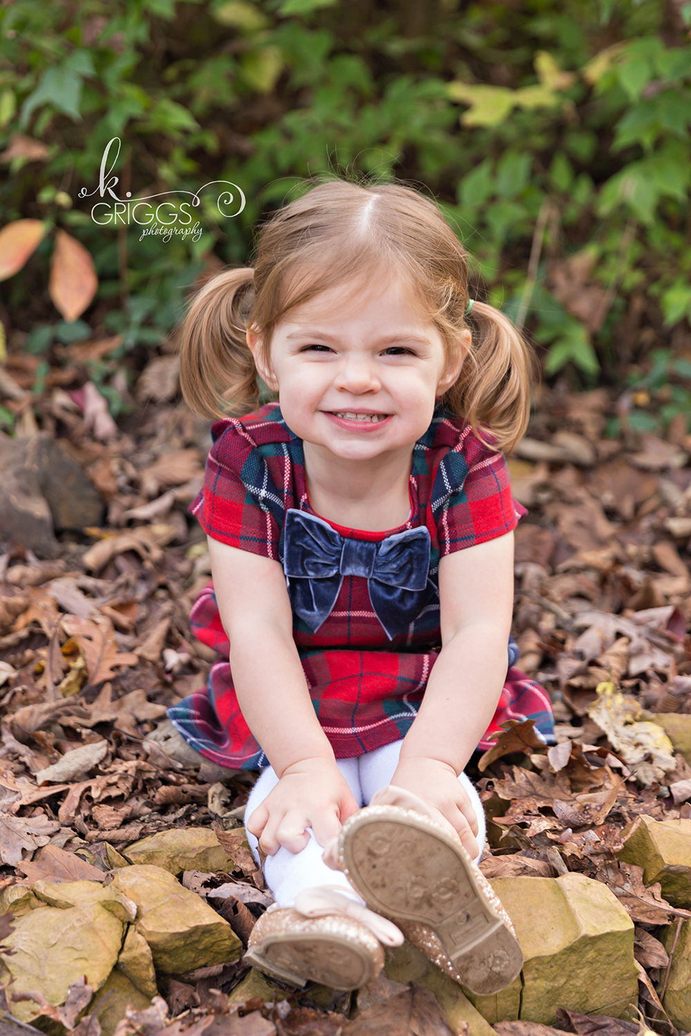 Young girl sitting in leaves smiling | St. Louis Family Photographer