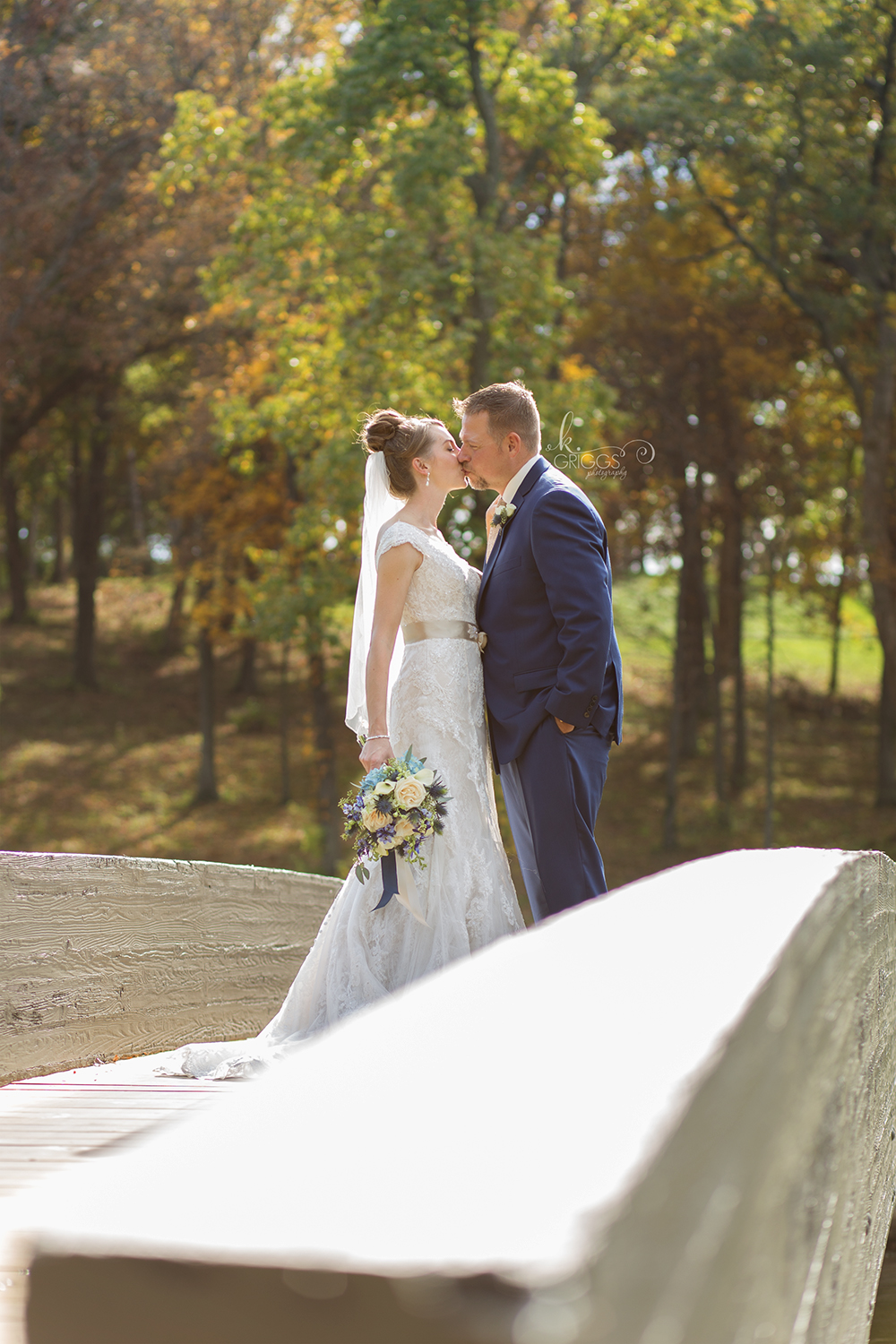 bride and groom standing on bridge kissing | St. Louis Photographers