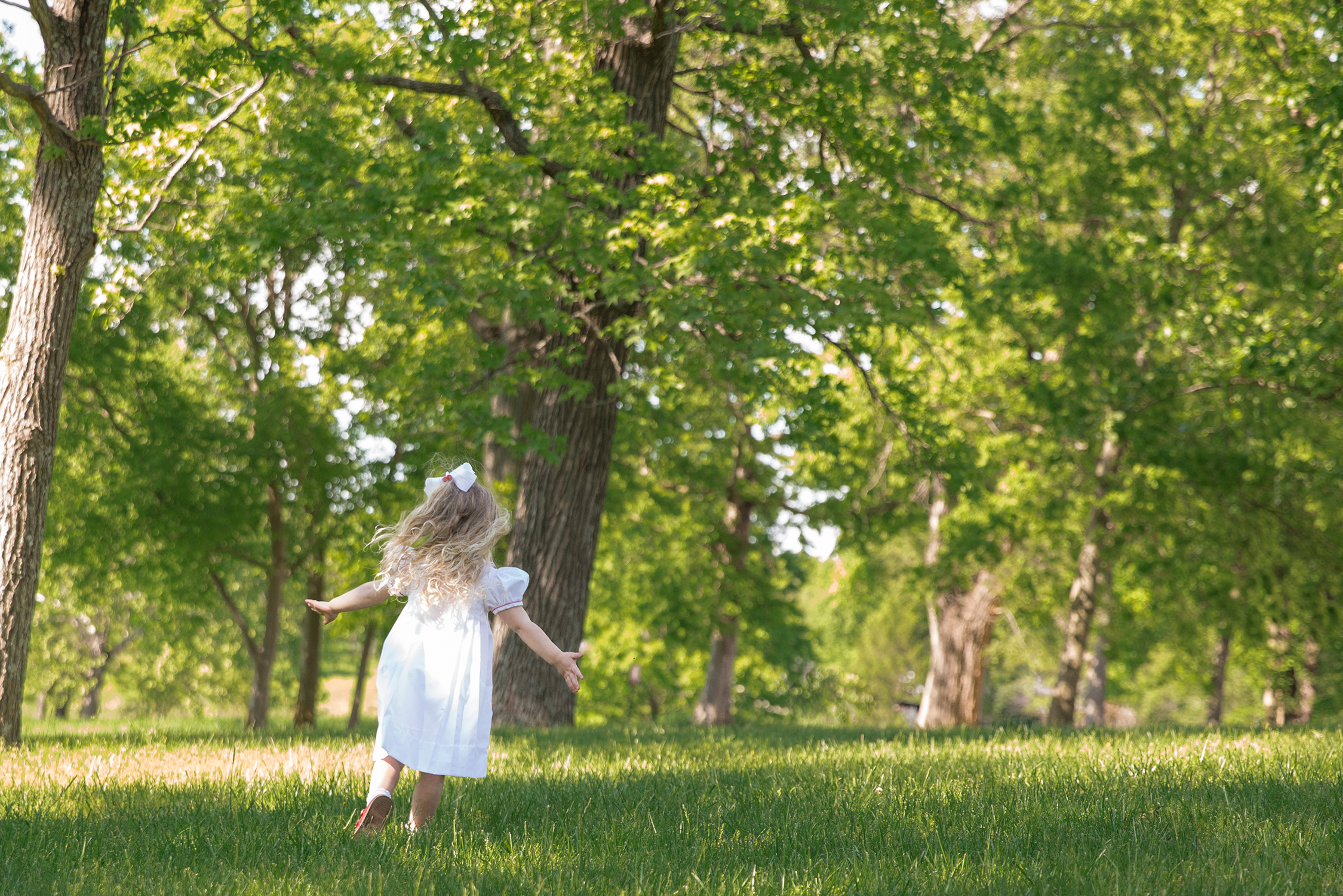 Little girl running and twirling in field | St. Louis Kids Portraits