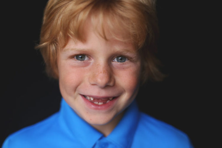 Boy with red hair smiling at camera - St. Louis School Photographer