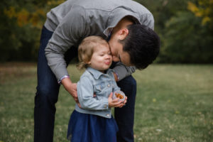 Little girl eating snack with her daddy at Larson Park - St. Louis family photos
