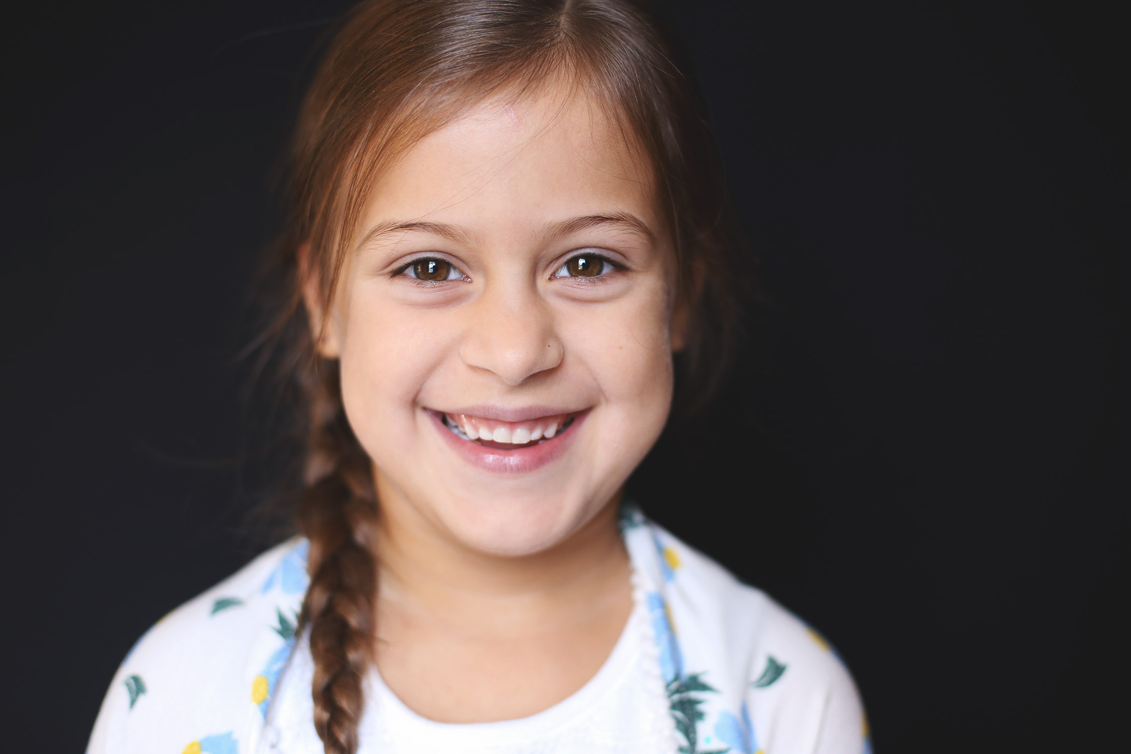 Young girl with braided hair smiling at camera   St. Louis School Photography
