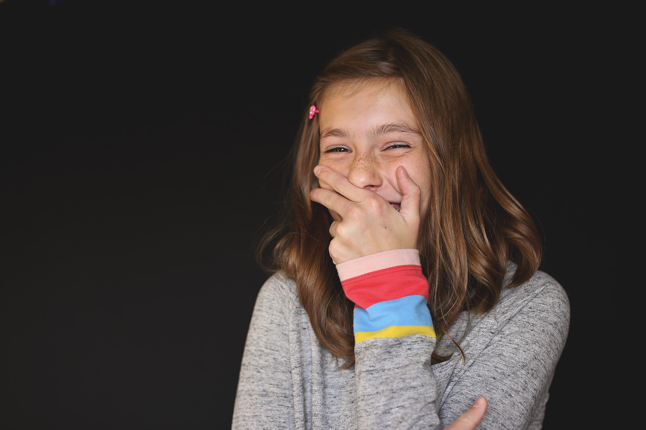 Tween girl covering her mouth while laughing   St. Louis School Photos