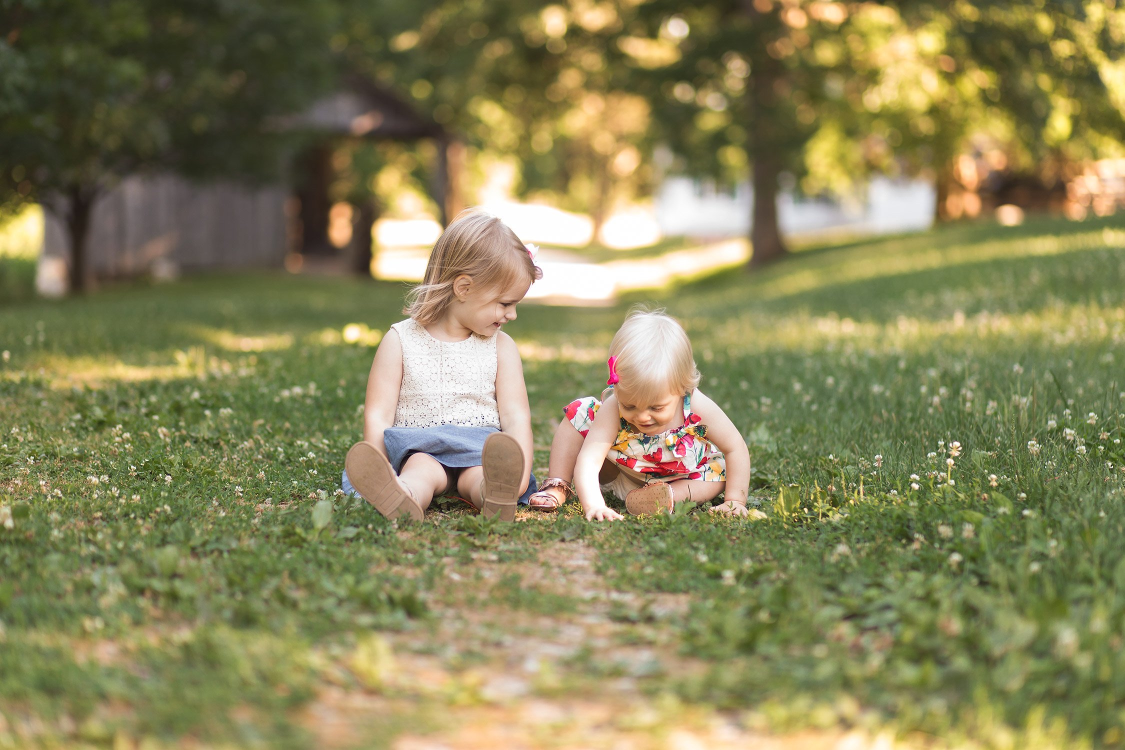 Sisters sitting in the grass in Faust Park | St. Louis Children's Photographer