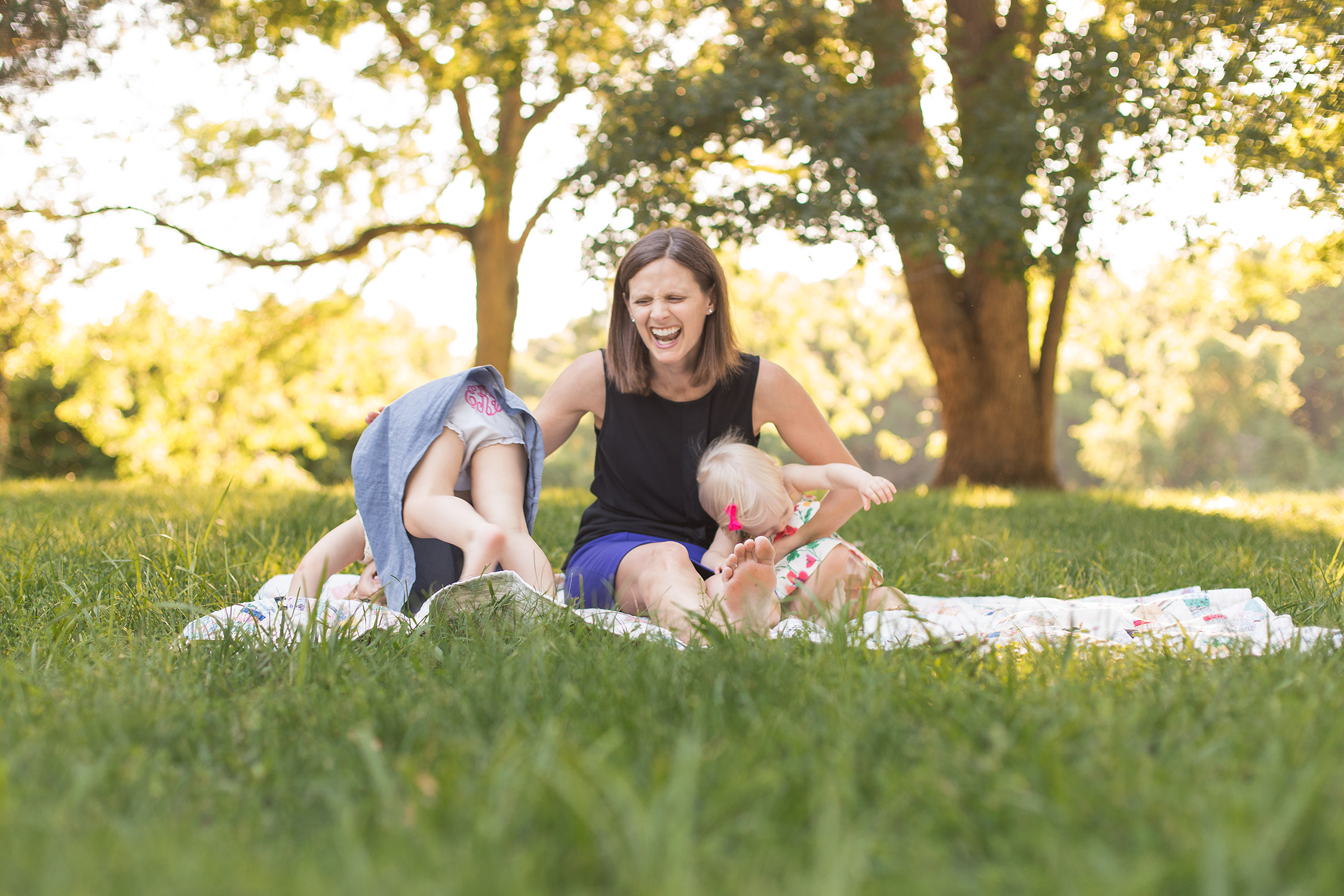 Mommy laughing at one of her daughters in Faust Park | St. Louis Family Photographer